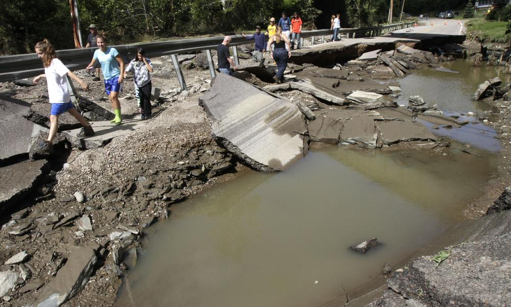 People walk along a section of Route 12 washed out by Hurricane Irene on Monday, in Berlin, VT. (AP)
