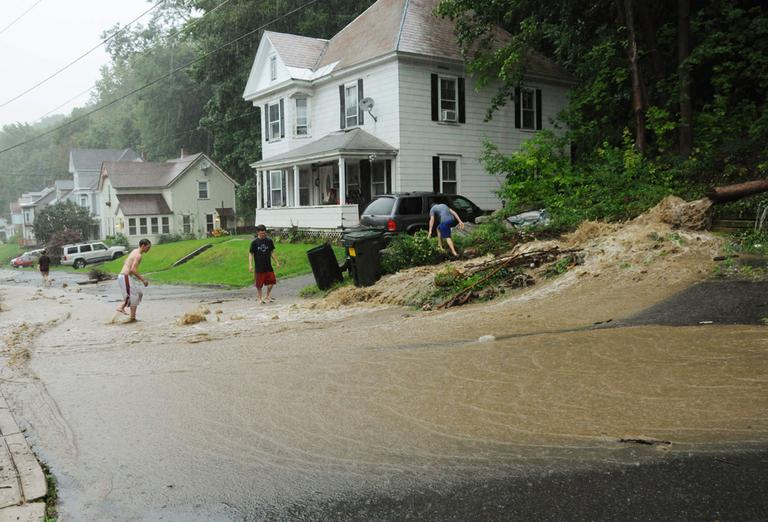 In this photo provided by Gregory Scheckler, floodwaters caused by Tropical Storm Irene rush down a street in North Adams, Mass., Sunday. (AP)