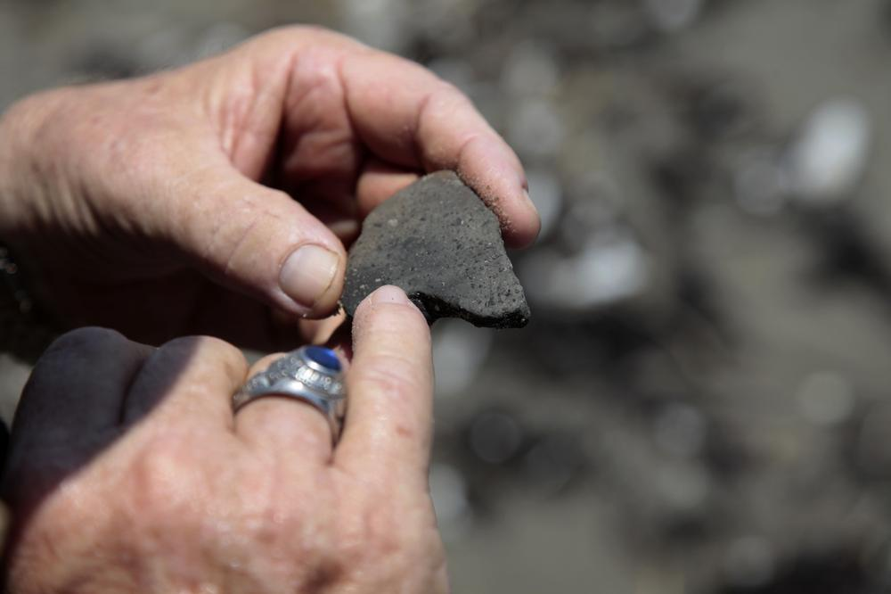 Forrest Travirca III, looks at an ancient pottery shard he found as he walks along Port Fourchon Beach searching for artifacts from Pre-historic American-Indian settlements in Caminada Headland, La. (AP)