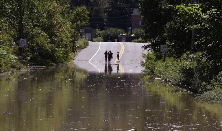 Children stand on the far side of a flooded portion of Massachusetts Rt. 5 which was closed to traffic in Northhampton, Mass., Monday. (AP)