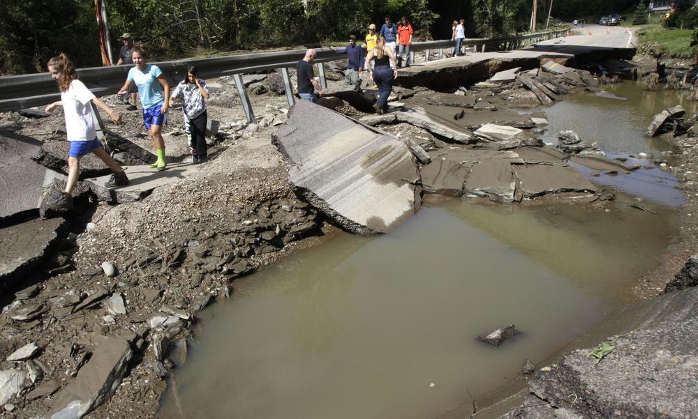 People walk along a washed out section of Route 12 on Monday, in Berlin, Vt. (AP)