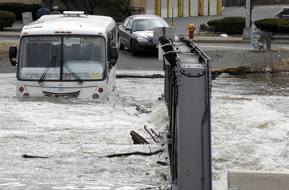 An Express Service bus is seen stuck on a small bridge in downtown Paterson, N.J., where high waters from the Passaic River made the crossing impossible, Sunday. (AP)