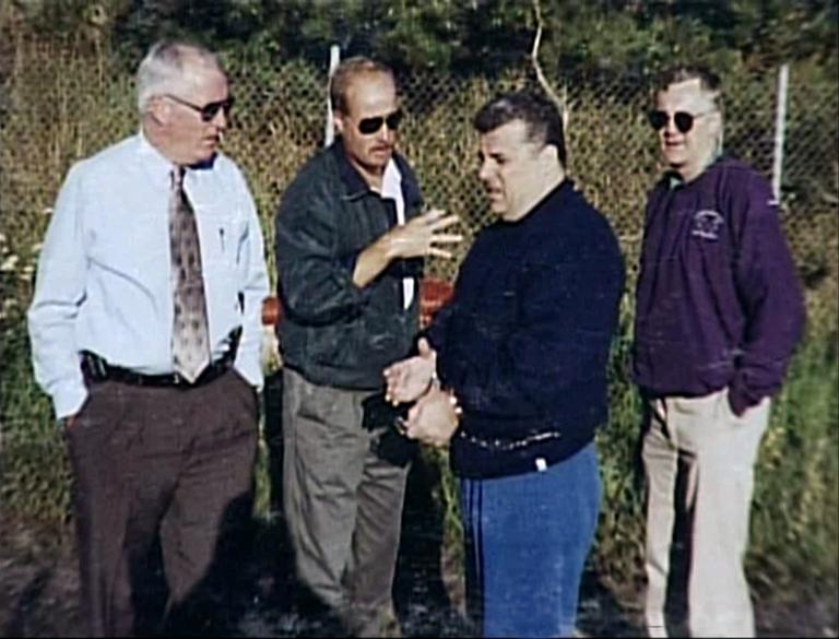 2005 file photo of Kevin Weeks, third from left, showing a burial site of alleged murder victims to, left to right: Col. Tom Foley, Mass. State Police; Daniel Doherty, DEA; and Lt. Steve Johnson, Mass. State Police (David Boeri/WBUR)