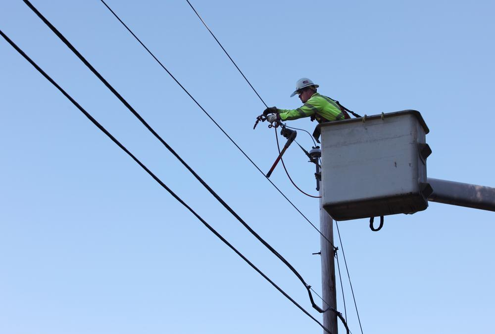 Steve Music works to replace a power line damaged by Tropical Storm Irene in Buxton, Maine Monday. (AP)