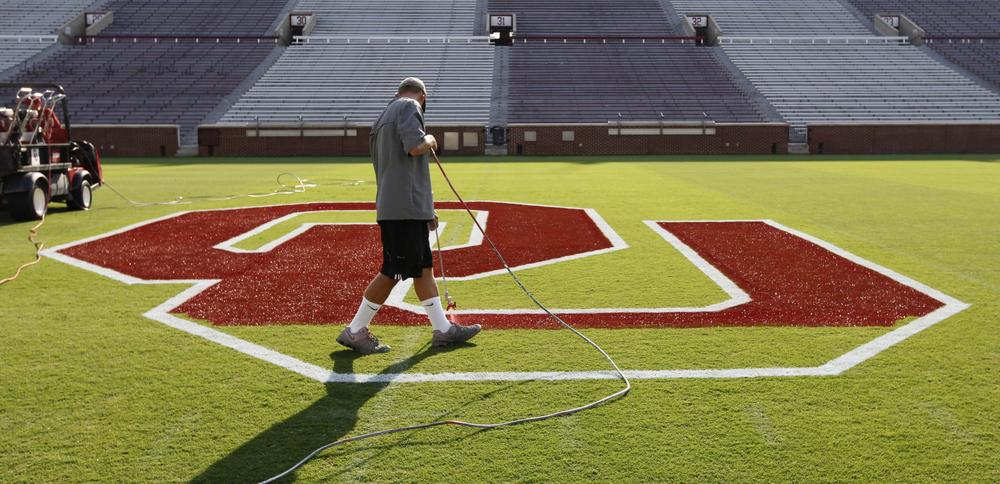 Oklahoma is ranked #1 going into this football season. A worker prepares Owen Field for the team's season opener on Saturday against Tulsa. (AP)