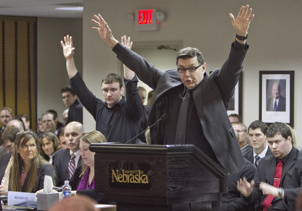 University of Nebraska at Omaha wrestling coach Mike Denney lifts his arms in protest in March as university regents unanimously approved the UNO's proposal to join the NCAA Division I Summit League.  (AP)