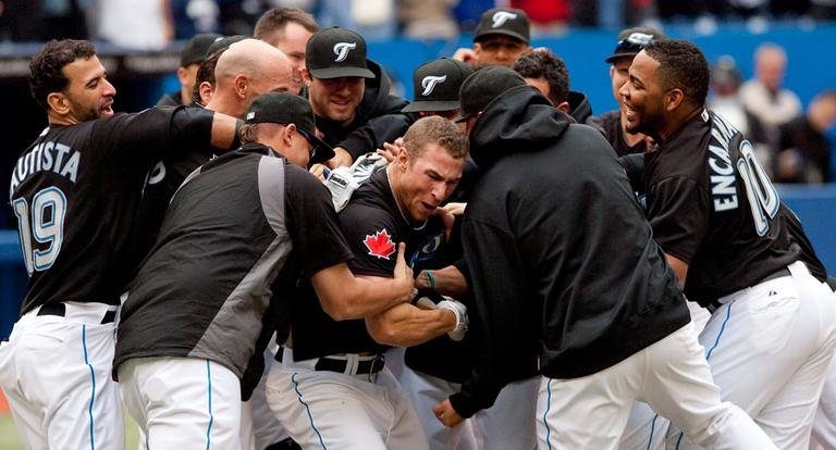 The Blue Jays' Brett Lawrie is mobbed by teammates after hitting a walk-off home run in their 1-0 win over the Red Sox Monday. (AP)