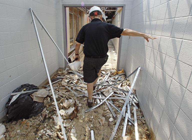 In this Aug. 24 photo, Bill McBride, the associate principal of Cathedral High School, climbs over debris while walking down a school corridor. (AP)