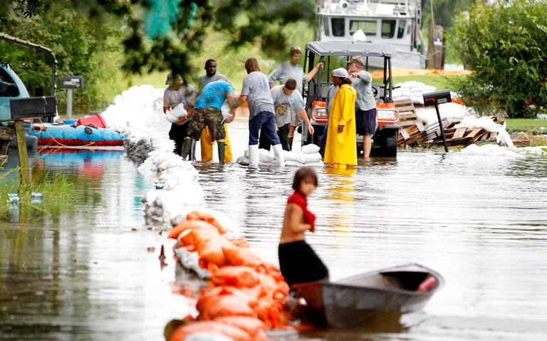 Parish crews placed sand bags along a flooded street in Lafitte, La., Sunday. (AP)