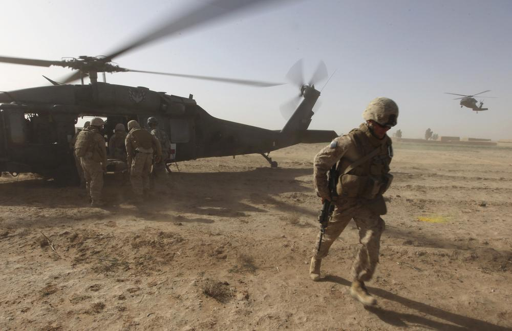 U.S. Marines help a wounded comrade onto a Black Hawk helicopter, left, during a medevac mission by the U.S. Army's 82nd Airborne's Task Force Pegasus, in 2010. (AP)