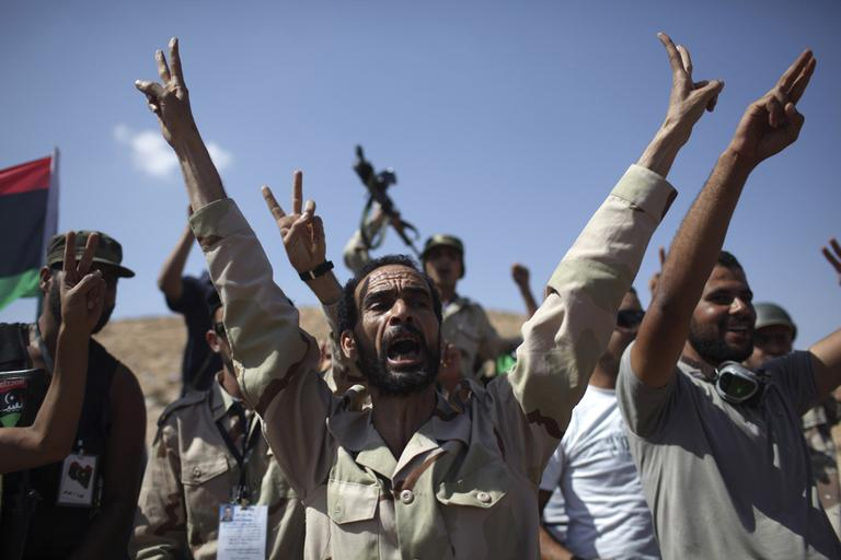 Rebel fighters shout slogans against Moammar Gadhafi at a checkpoint between Tarhouna and Bani Walid, Libya, Wednesday. (AP)