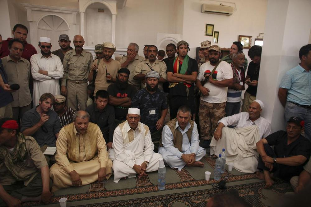Tribal elders, bottom, speak to Abdalla Kenshil, chief rebel negotiator, in a mosque at a checkpoint between Tarhouna and Bani Walid on Tuesday. (AP)