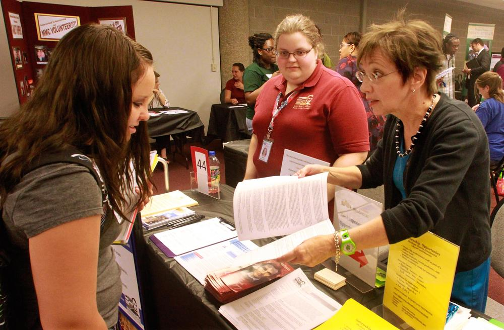 Alyssa Wright, left, speaks with Carol Manning, right, and Molly Ralston, center, about career opportunities at the Abraham Lincoln Presidential Library and Museum booth during a job fair at the University of Illinois Springfield campus. (AP)