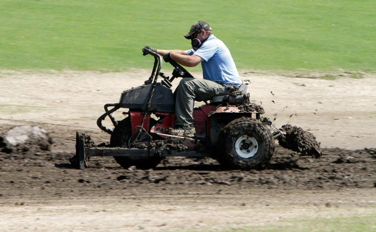 Following Tropical Storm Irene, Scott Burton tries to move mud off the golf course at the Woodstock Inn resort on Friday in Woodstock, Vt., near West Hartland, Vt. (AP)