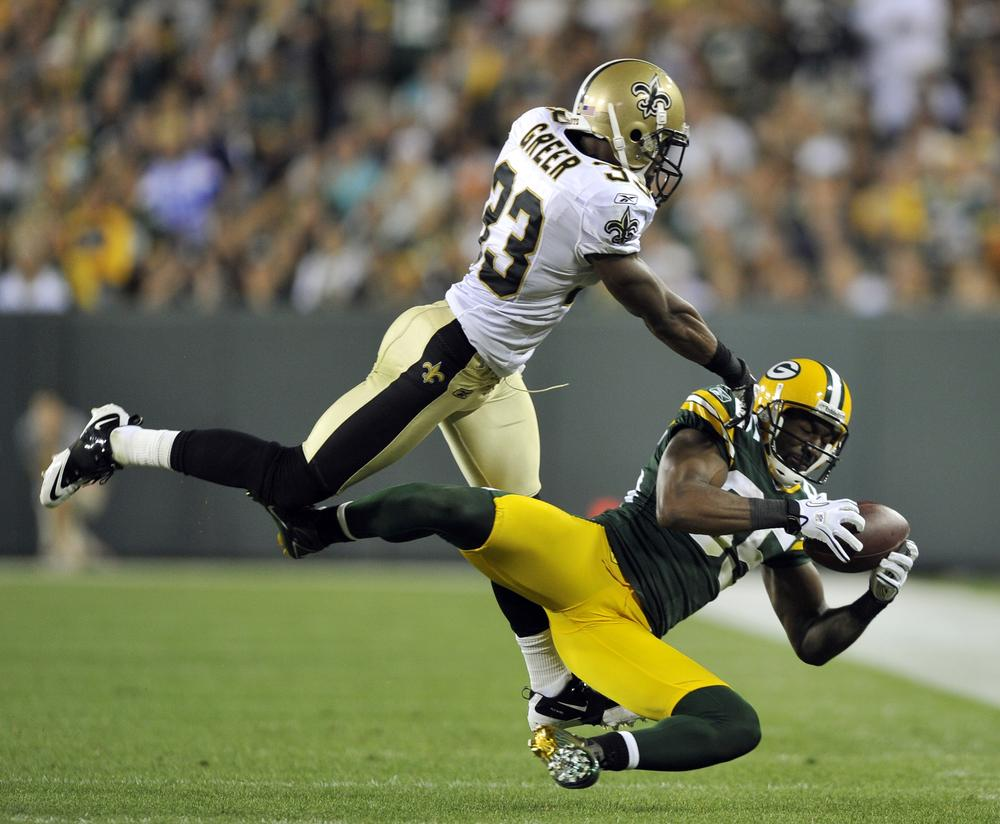 Greg Jennings of the Green Bay Packers catches a pass in front of New Orleans Saints' Jabari Greer during the second half of the NFL season opener on Thursday night in Green Bay. (AP)