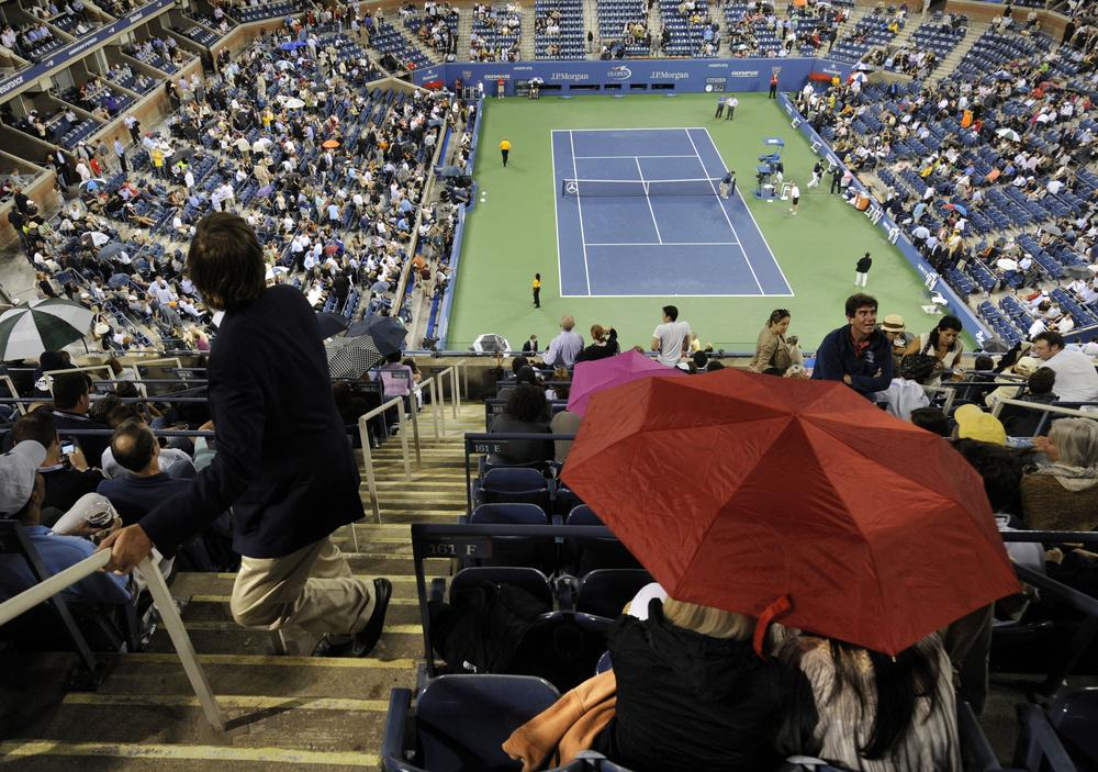 Some spectators leave their seats while others take shelter under umbrellas in Arthur Ashe Stadium during a rain delay at the U.S. Open on Thursday. (AP)