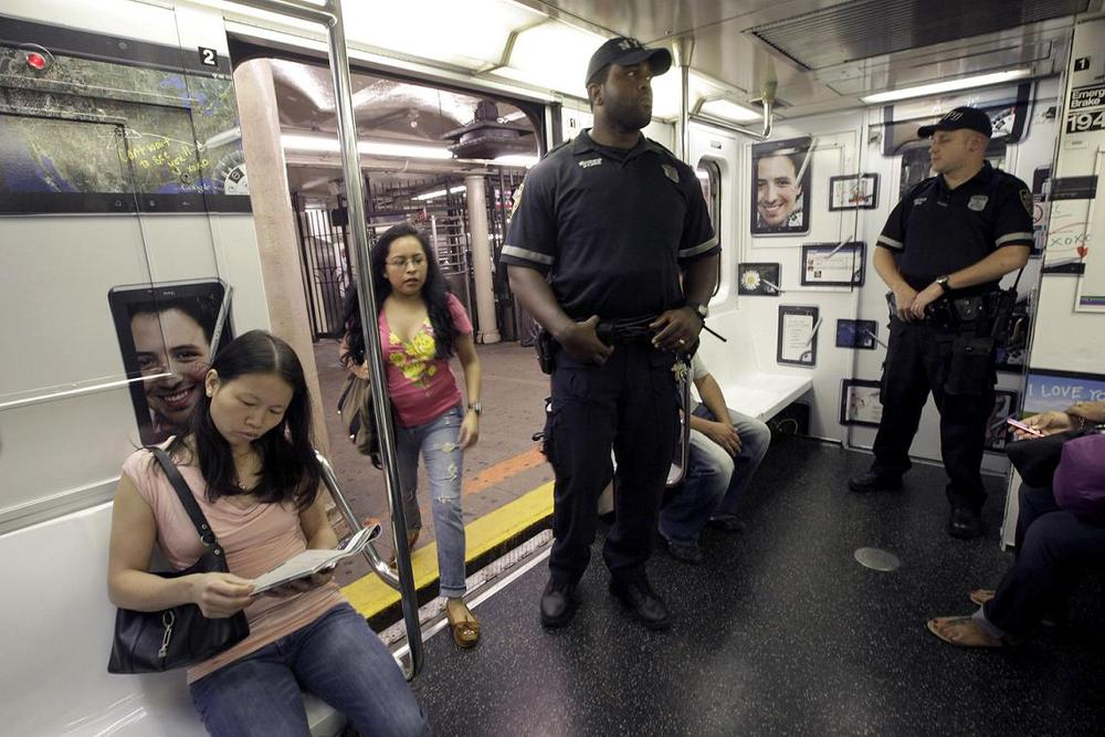 Police officers ride the shuttle between New York's Times Square and Grand Central Station, Friday. (AP)