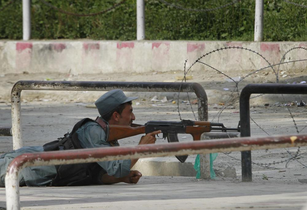 An Afghan policeman takes position near the building which is occupied by militants, unseen, in Kabul, Afghanistan on Tuesday. (AP)