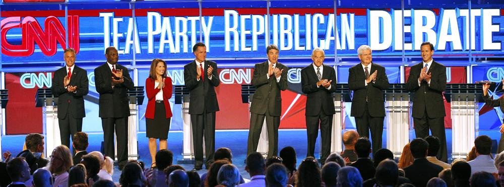 Republican presidential candidates, from left, Utah Gov. Jon Huntsman, businessman Herman Cain, Rep. Michele Bachmann, R-Minn., former Massachusetts Gov. Mitt Romney, Texas Gov. Rick Perry, Rep. Ron Paul, R-Texas, former House Speaker Newt Gingrich, and former Pennsylvania Sen. Rick Santorum, applaud before a Republican presidential debate Monday in Tampa, Fla. (AP)
