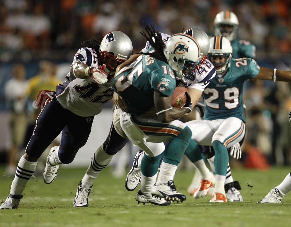 New England players Benjarvus Green-Ellis (42) and Danny Aiken (48) tackle Miami's Davone Bess (15) during the first half of the game in Miami on Monday. New England won 38-24. (AP)