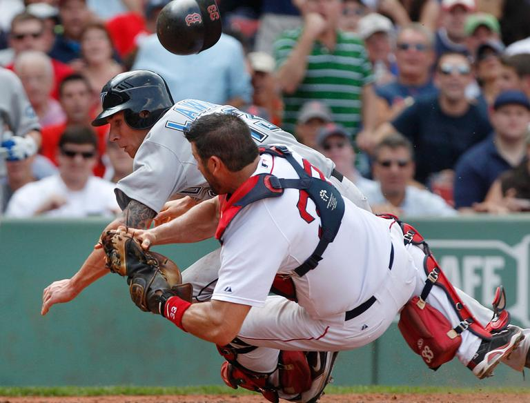 Sox catcher Jason Varitek loses his helmet but hangs onto the ball as he collides with Blue Jay Brett Lawrie, who unsuccessfully tried to score on a fielder's choice during the sixth inning Wednesday. (AP)