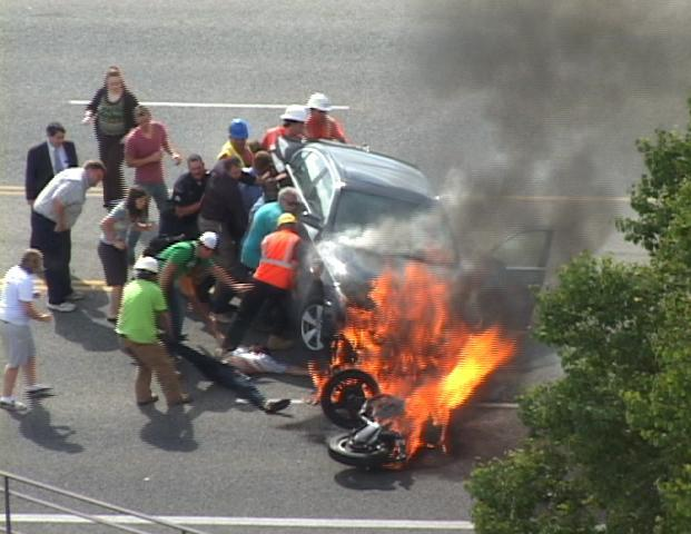 A group of people tilt a burning BMW up to free Brandon Wright, on his back on the ground, who was pinned underneath after he collided with the car while riding his motorcycle on U.S. 89 in Logan, Utah. Wright survived. (AP)