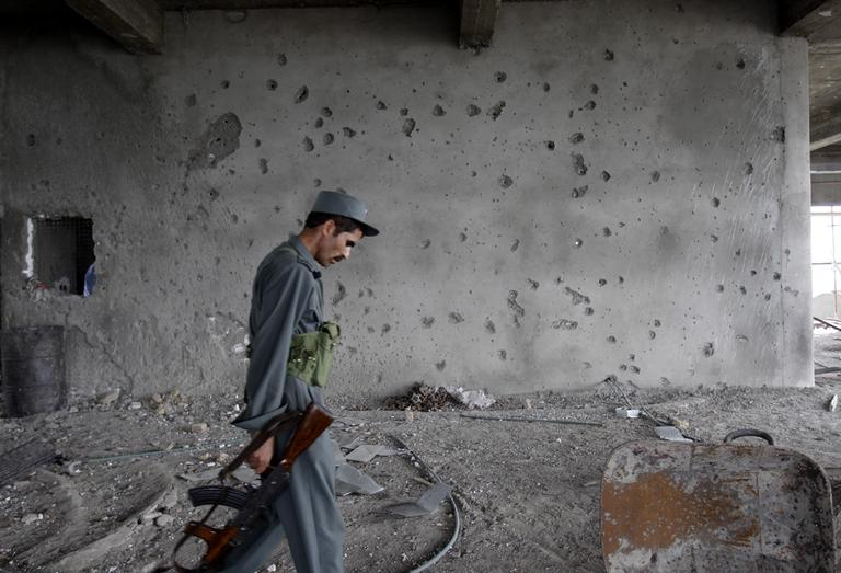 An Afghan police officer passes by a shattered wall of the building which was occupied by Taliban militants during the insurgent attack in Kabul on Wednesday. (AP)