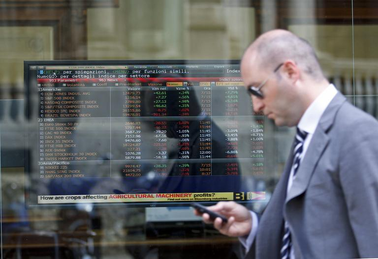 A man passes close to a stock exchange board monitor inside a bank in Milan, Italy.  Worries that Europe's debt crisis will spread to Italy and Spain weighed on markets . (AP)