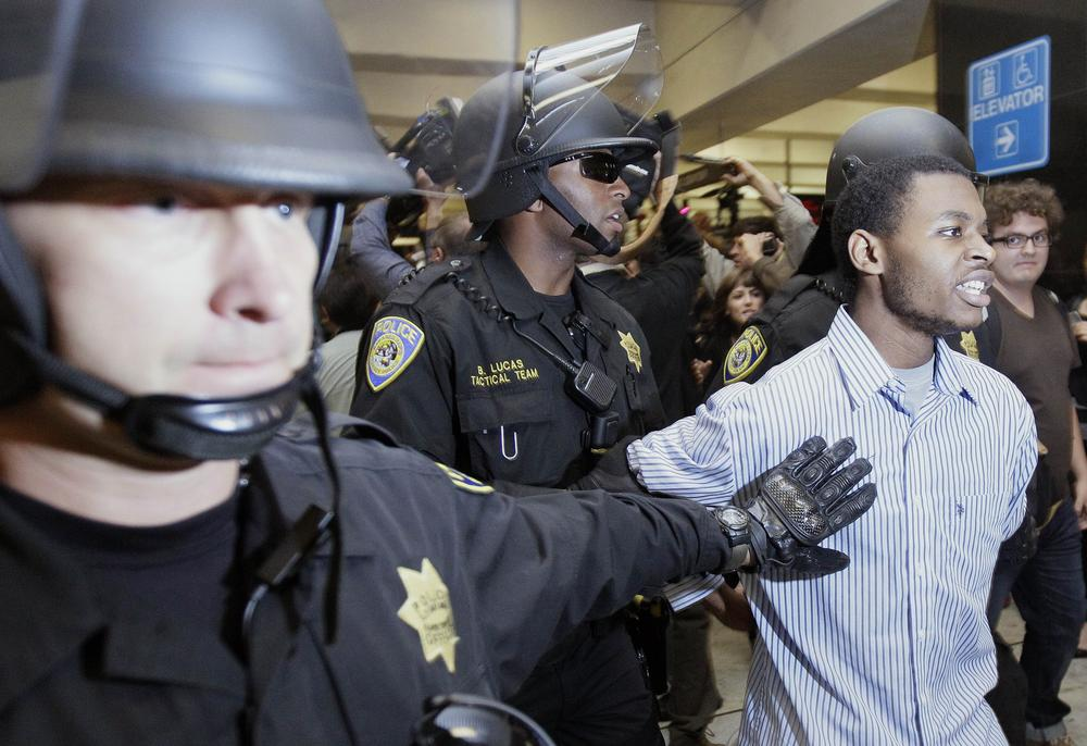 Bay Area Rapid Transit (BART) police officers arrest a man during a protest at the Civic Center train station in San Francisco. (AP)