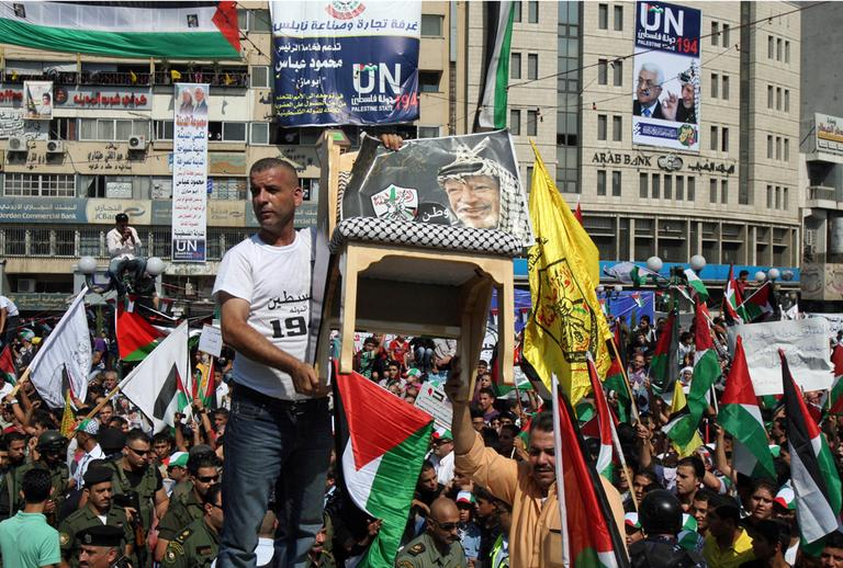 Palestinians hold up a chair with a picture of late Palestinian leader Yasser Arafat and wave flags during a rally in support of the Palestinian bid for statehood recognition in the United Nations, in the West Bank city of Nablus, Wednesday, Sept. 21, 2011. (AP)