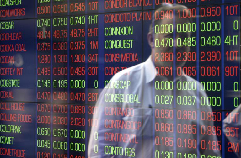 A man watches through a window as display boards at the Australian Stock Exchange flash news of a falling market in Sydney on Friday (AP)