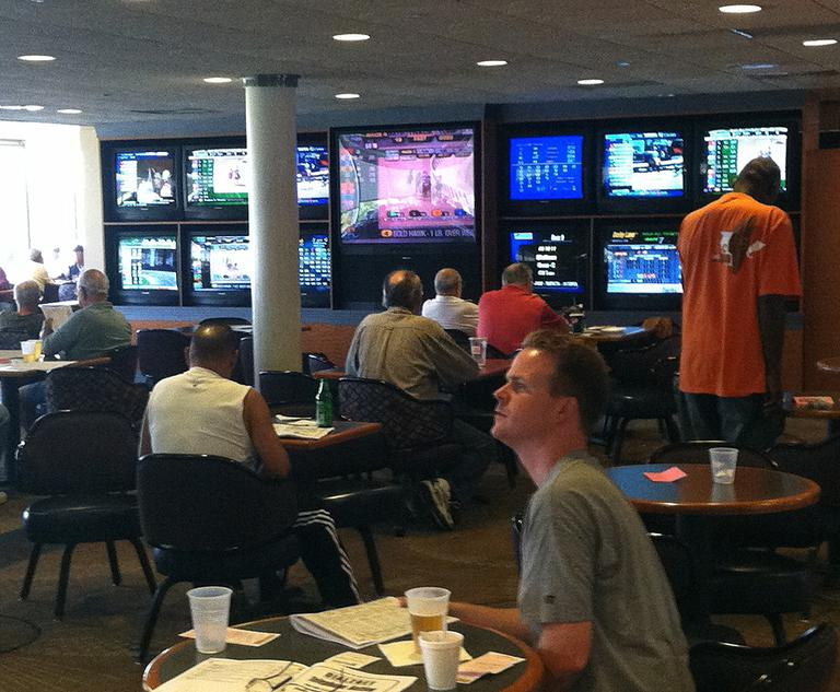 About 100 or so people watch muted TV screens in the clubhouse of Raynham Park. (Steve Brown/WBUR)