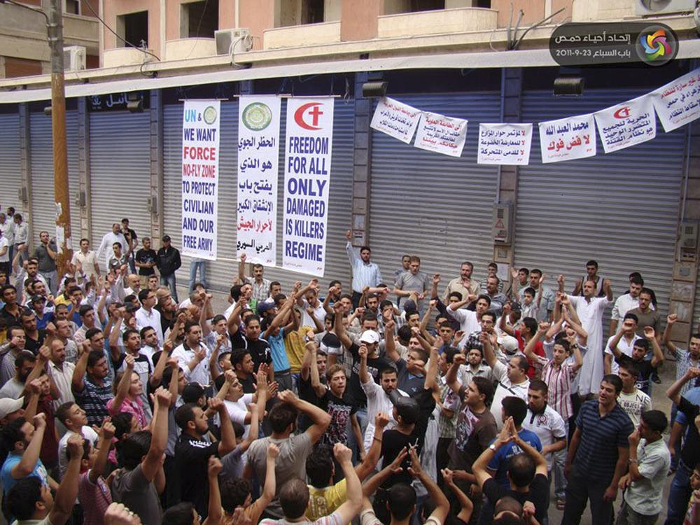 "In this citizen journalism image made on a mobile phone and provided by Homs Quarters Union, protesters shout slogans during a demonstration against the Syrian regime, in Homs province, Syria, on Friday. The Arabic banner in the center background reads:""A no-fly zone opens the door for the free soldiers of the Syrian army to defect."" (AP/Homs Quarters Union)"