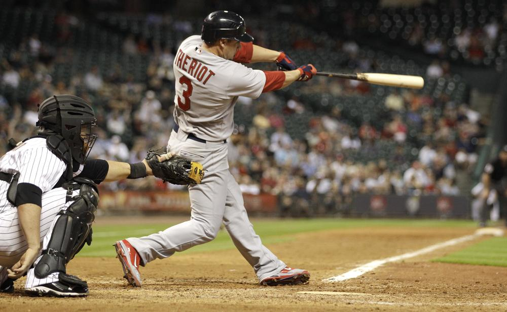 St. Louis Cardinals' Ryan Theriot (3) hits a two-run triple as Houston Astros catcher Humberto Quintero, left, reaches for the pitch during the seventh inning of a baseball game Tuesday. (AP)