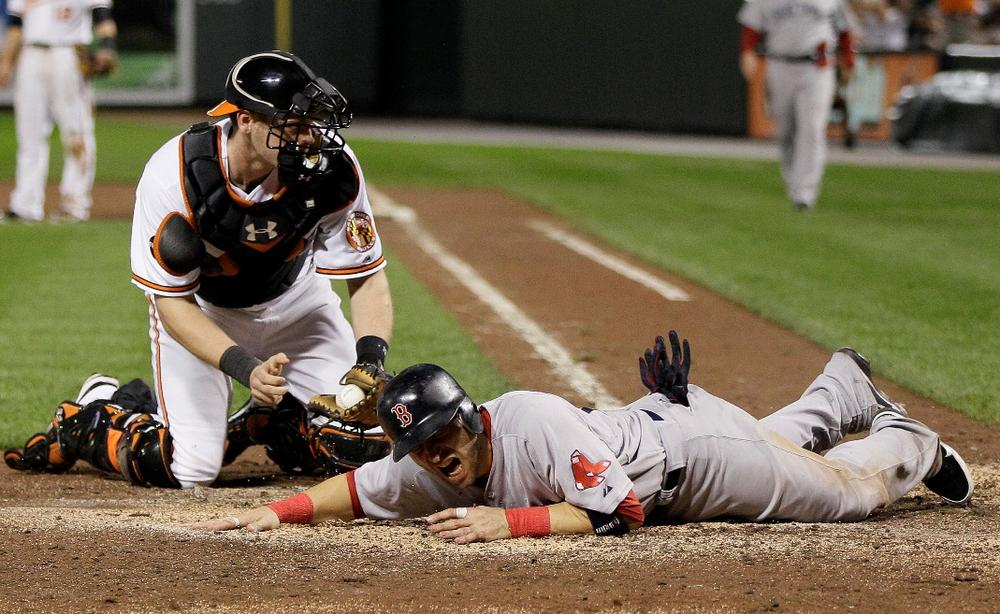 The Red Sox' Marco Scutaro was tagged out at the plate in a crucial eighth-inning play. (AP)