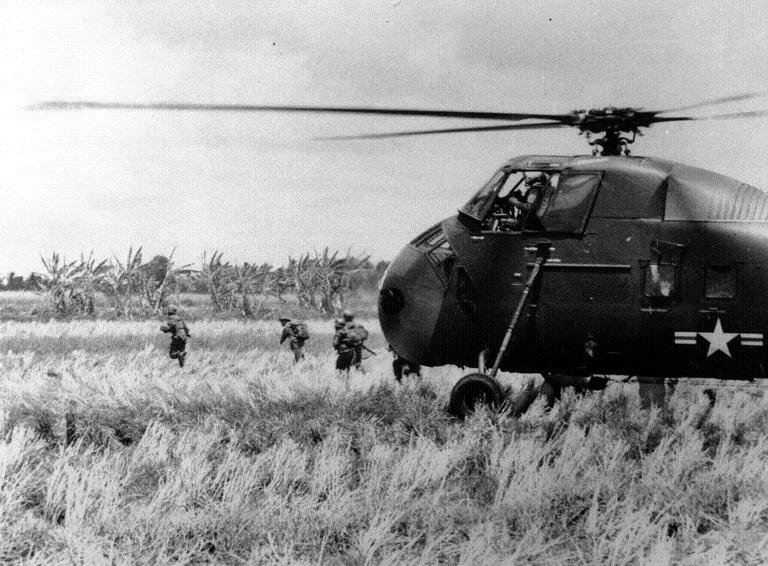 South Vietnamese troops, airlifted to an attack on Viet Cong guerrillas in the Mekong River Delta area, run from a US helicopter in May 14, 1962. (AP)