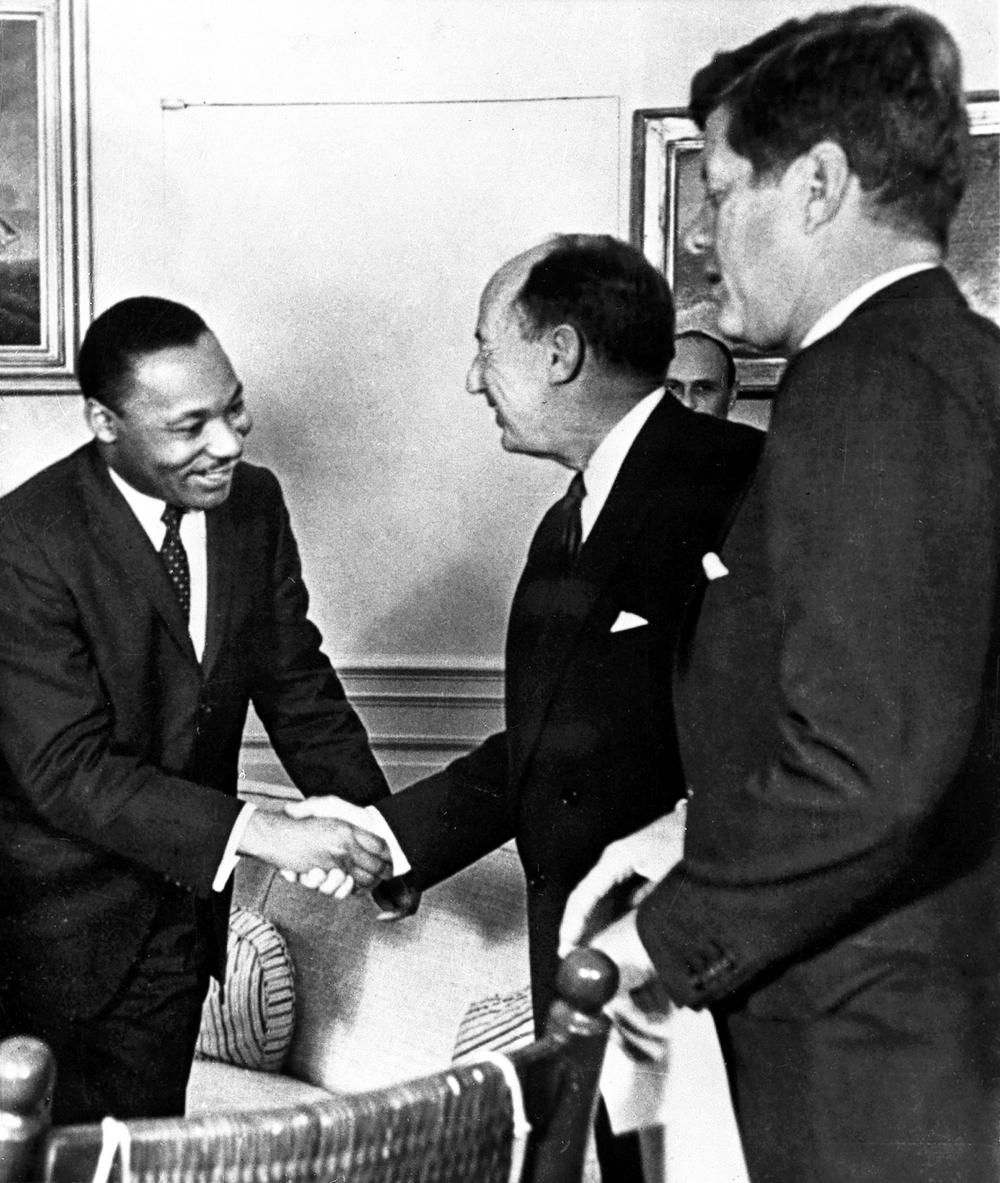 Martin Luther King Jr. shakes hands with Adlai Stevenson, then the U.S. delegate to the United Nations, as President John F. Kennedy looks on, in 1962. (AP)