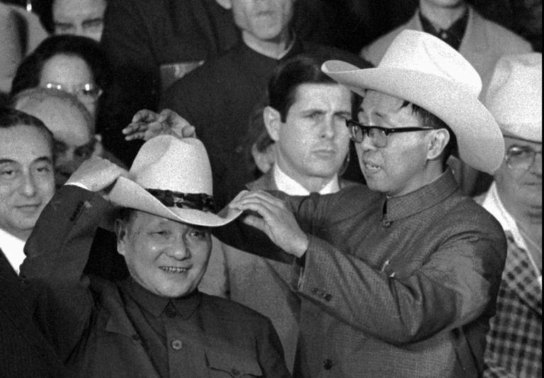 An aide helps then Chinese Vice Premier Deng Xiaoping try on a cowboy hat presented to him at a rodeo in Simonton, Texas Feb. 2, 1979. (AP)