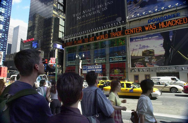 People watch news about the attacks scroll by in New York City's Times Square. (AP)