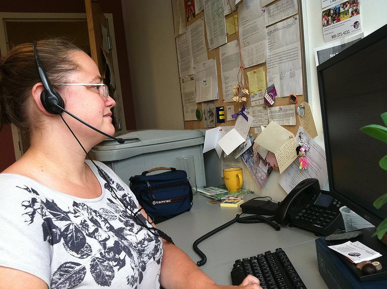 Kate Bicego talks to callers who need health coverage at Health Care For All. (Martha Bebinger/WBUR)