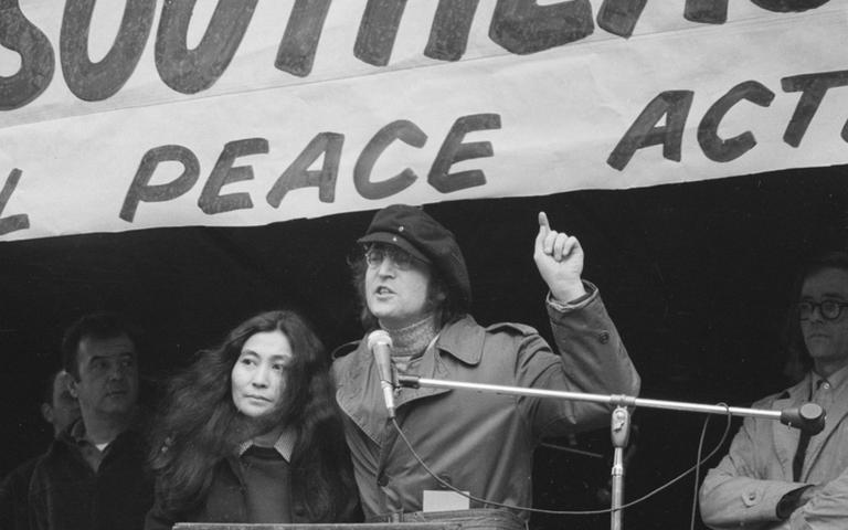 Former Beatle John Lennon, right, gestures as he speaks at a peace rally in New York's Bryant Park on April 22, 1972. Standing beside him is his wife, Yoko Ono. The rally and march of some 30,000 persons in New York City is part of a nationwide day of protests and demonstrations against U.S. involvement in the Vietnam War. (AP)