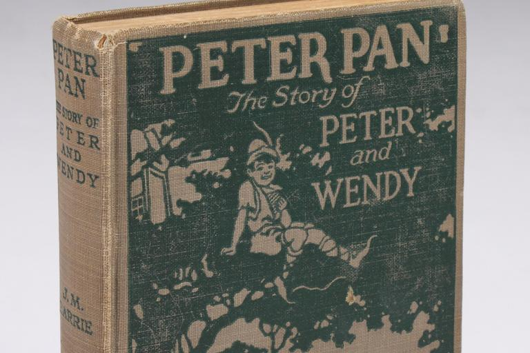 """This photo released by Julien's Auctions shows a 1911 Grosset and Dunlap edition of """"Peter Pan: The Story of Peter and Wendy,"""" by J.M.Barrie, with embossed cover and scenes from the photoplay featuring Betty Bronson. (AP)"""