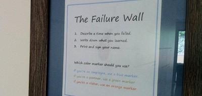 "Instructions for the Dun & Bradstreet Credibility Corp. ""Failure Wall."" ""Describe a time when you failed, write down what you learned, print and sign your name. If you're an employee, use a blue marker. If you're a partner... green...A visitor... orange."" (Courtesy of Dun & Bradstreet Credibility Corp.)"