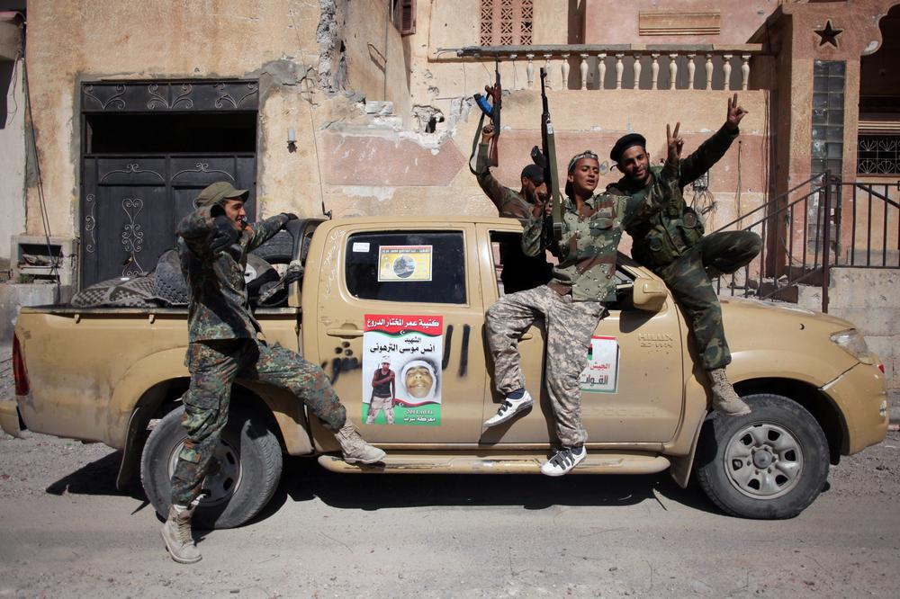 Revolutionary fighters celebrate the capture of Sirte, Libya, Thusday. Officials in Libya's transitional government said Moammar Gadhafi was captured and possibly killed Thursday when revolutionary forces overwhelmed his hometown, Sirte. (AP)