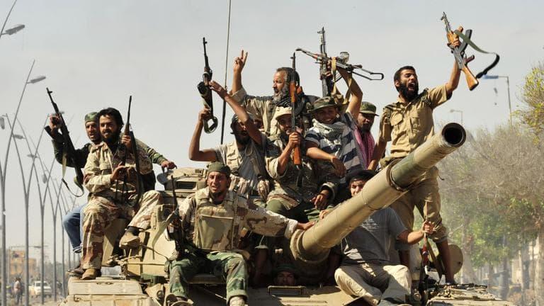 Anti-Gadhafi fighters celebrate the fall of Sirte in the town. (AP)