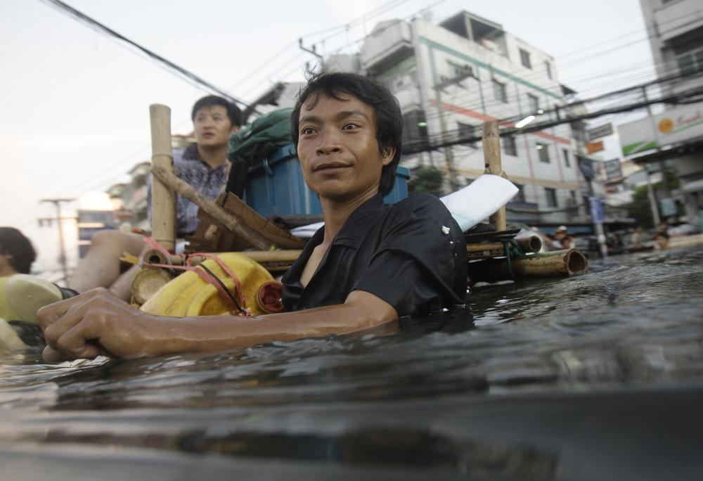 A Thai man wades along chest-deep floodwaters in the outskirts of Bangkok, Thailand on Thursday. (AP)