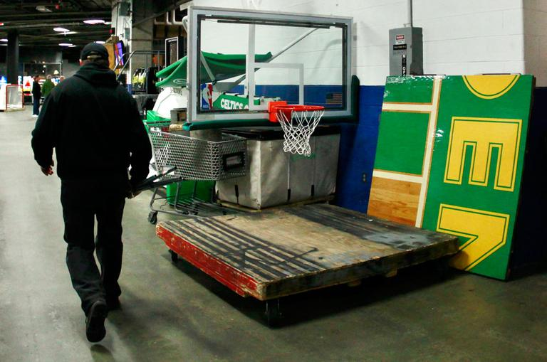 A TD Garden worker walks by a piece of the Boston Celtics parquet floor and a folded-up NBA basket on Oct. 5. The NBA lockout continues into November. (AP)