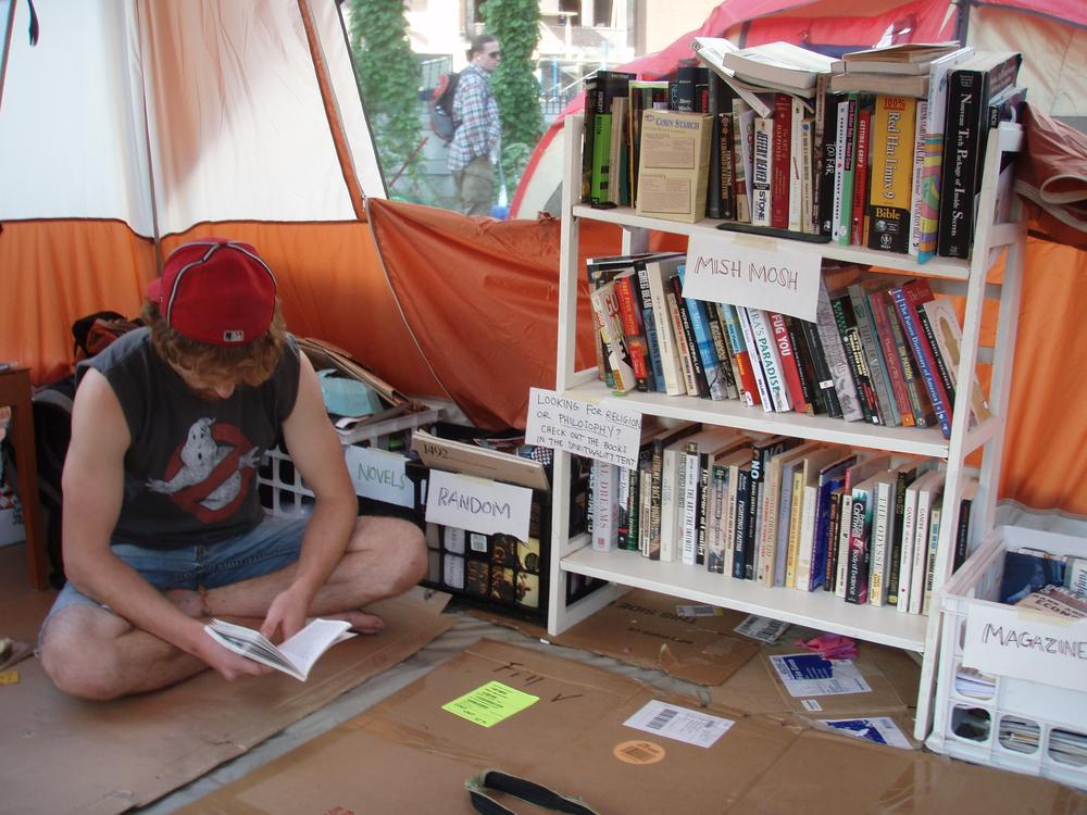 Occupy Boston protester Sean Eason reads Noam Chomsky in the camp's library tent. (Curt Nickisch/WBUR)