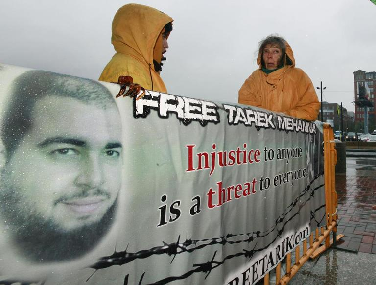 Tarek Mehanna supporters stand in the rain with a sign outside of U.S. District Court in Boston, Oct. 27. (AP)
