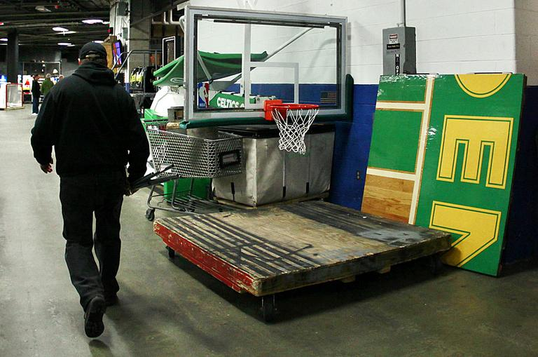 A TD Garden worker walks by a piece of the Boston Celtics parquet and a folded up NBA basket in Boston. (AP Photo/Elise Amendola)